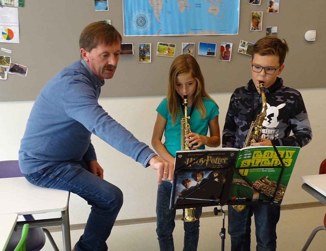 Gert leert zijn studenten de kneepjes van het saxofoon spelen